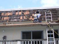 Professional employee of Lions Painting LLC repairing roof shingles in Honolulu, Hi