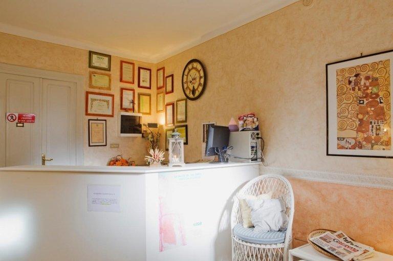 Reception con scrivania alta di color bianco,monitor,computer, dei quadri appesi e una sedia in paglia bianca ad Aosta