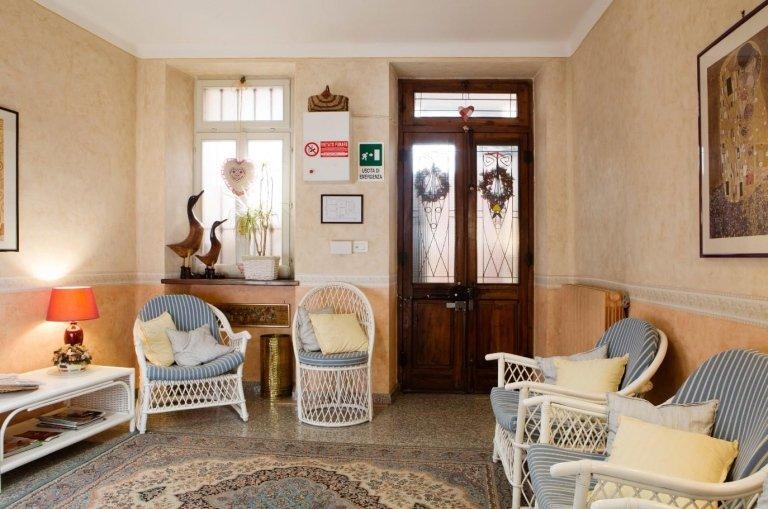 Vista della saletta d'attesa con sedie di paglia bianche,cuscini azzurri, due aironi in legno vicino alla finestra e un tavolino con sopra una lampada ad Aosta