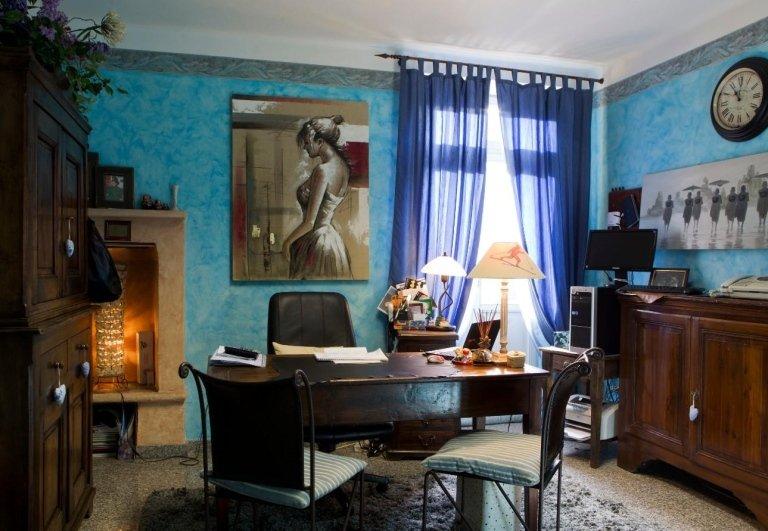 Ufficio con scrivania in legno, una lampada, un ritratto in bianco e nero di una donna  e un tavolino con sopra computer e monitor ad Aosta