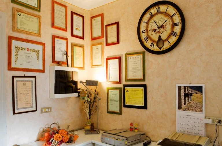 Stanza con un mazzo di fiori sulla scrivania e appesi al muro dei titoli e dei riconoscimenti in cornici e un orologio  ad Aosta