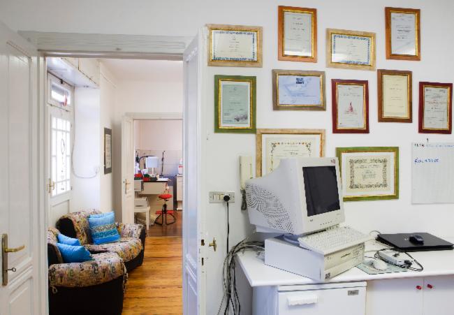 Scrivania bianca con computer, titoli e riconoscimenti appesi al muro e da una porta aperta si intravede un'altra stanza con un divano ad Aosta