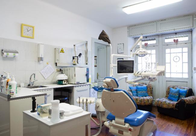 Sala operatoria con lettino reclinabile lavandino e banco con prodotti odontoiatrici ad Aosta