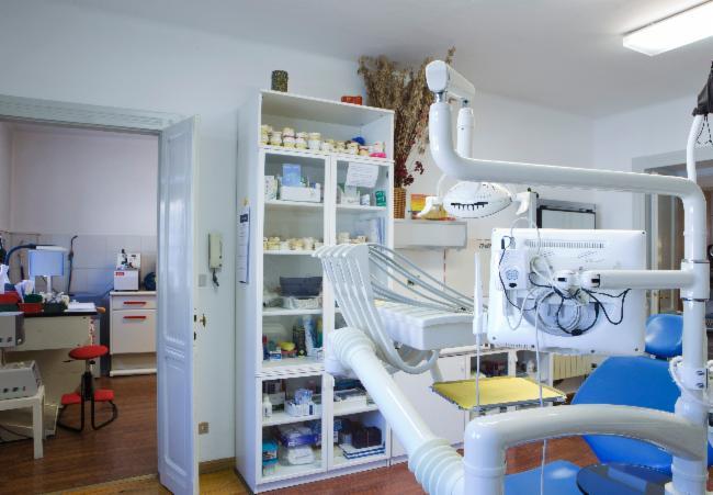 Vista della sala operatoria con armadietto in vetro con i prodotti il retro di un monitor con cavi a vista e lettino reclinabile blu ad Aosta ad Aosta