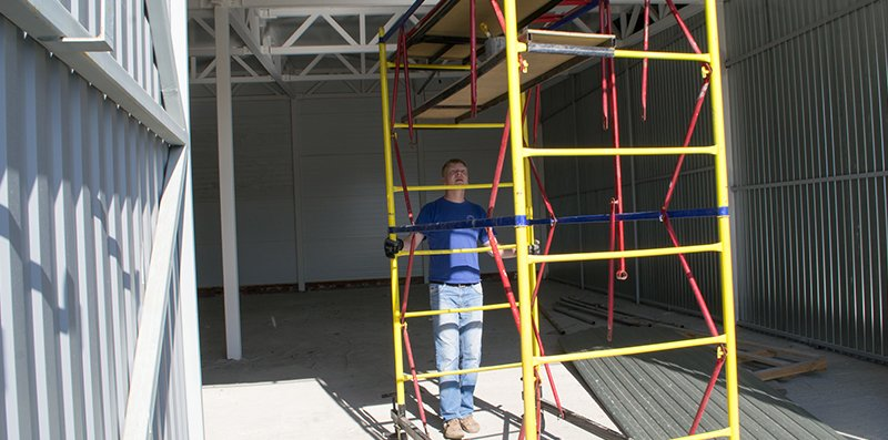 The installer moves the scaffolding at a different location