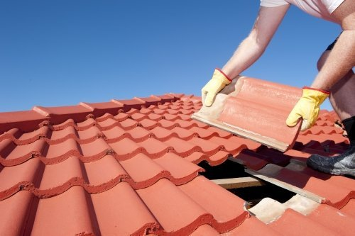 Roof repair worker with yellow gloves replacing red tiles