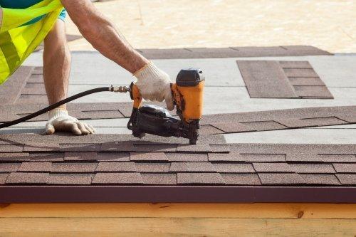 Construction worker putting the asphalt roofing