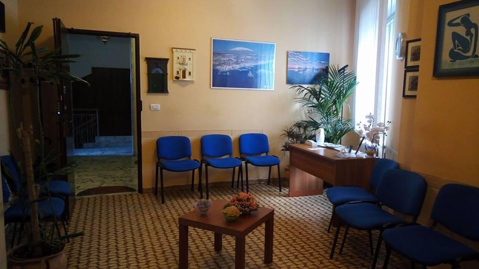 una sala d'attesa con delle sedie blu e sulla destra una scrivania marrone