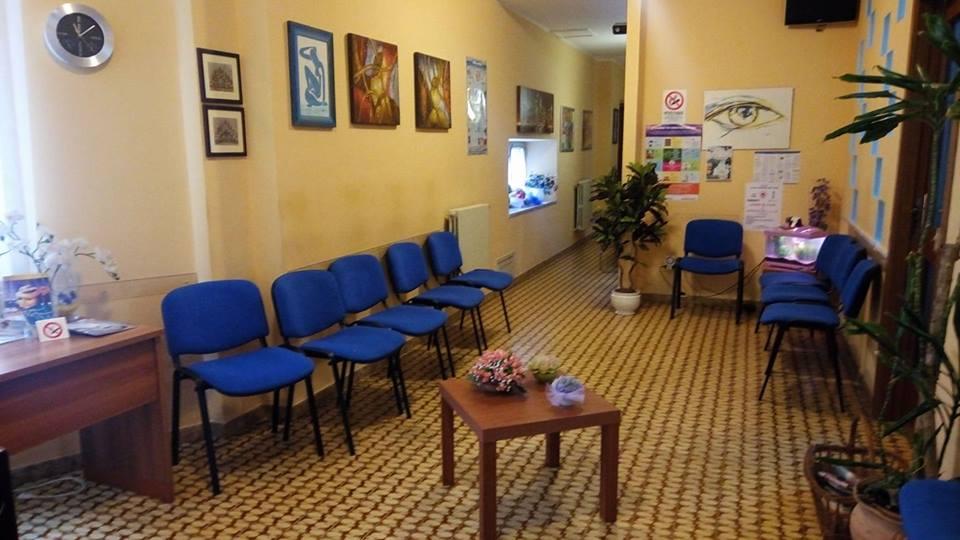 una sala d'attesa con delle sedie blu e un tavolino al centro