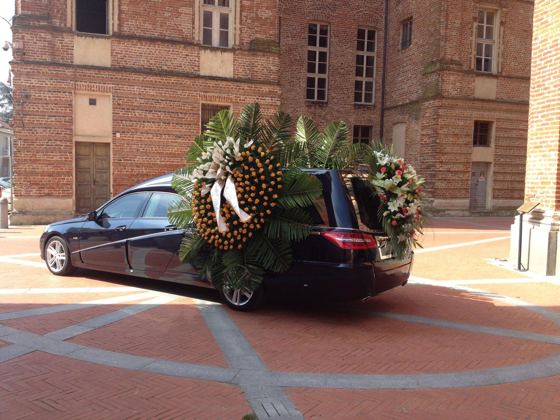 Auto funebre addobbata con corone di fiori