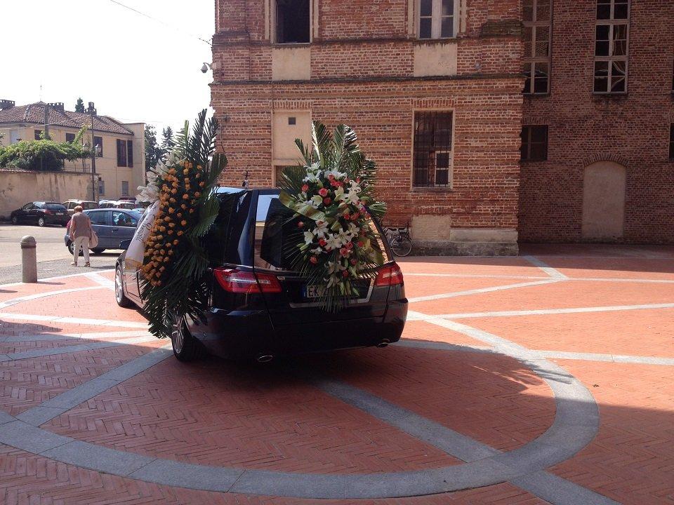 Carro funebre addobbatto, parcheggiato in una piazza