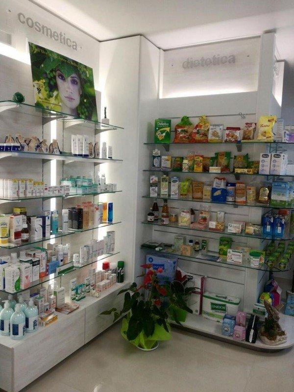 dei prodotti esposti su delle mensole di vetro in una farmacia
