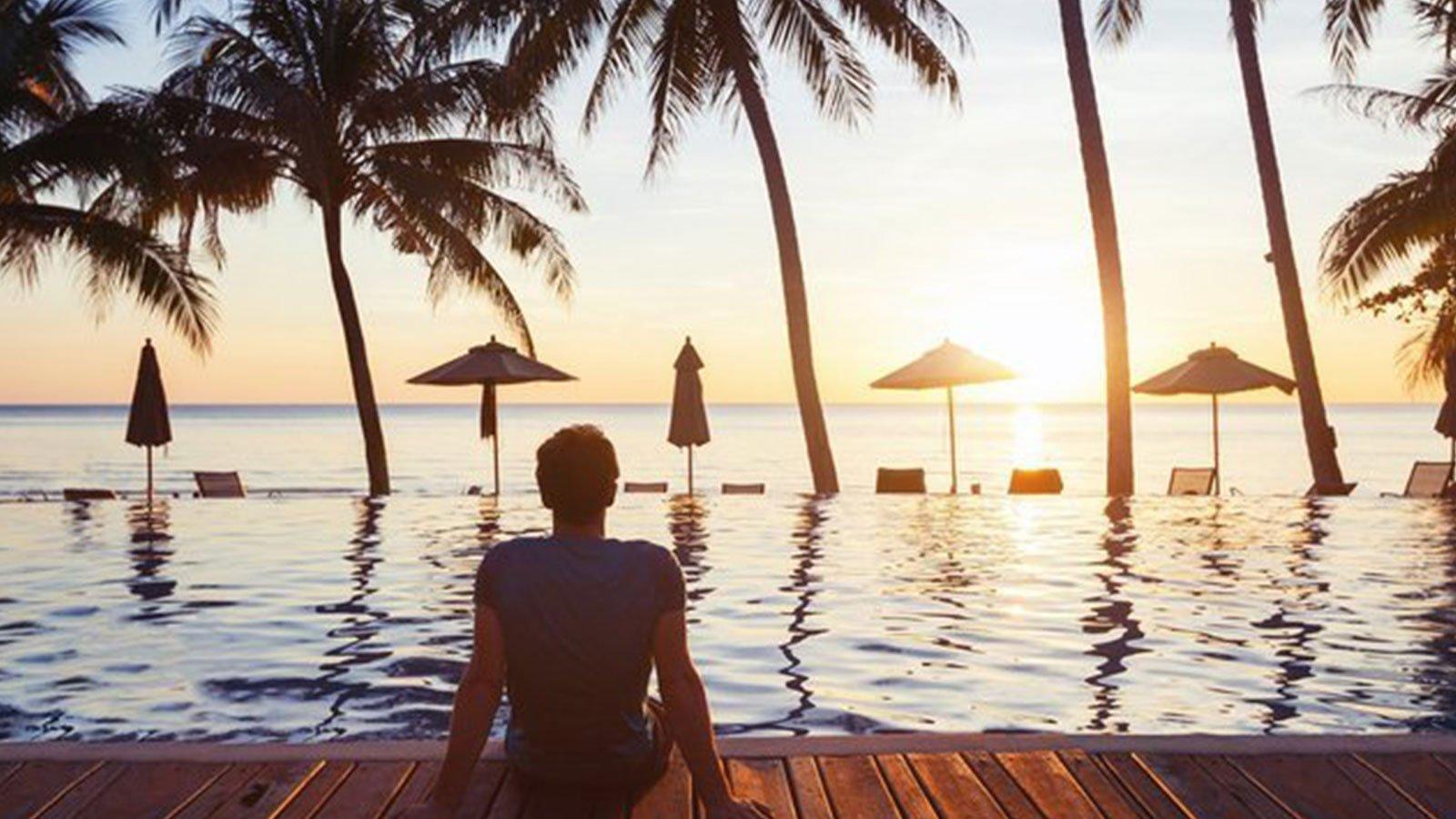un uomo seduto davanti a una piscina con vista del mare e degli ombrelloni