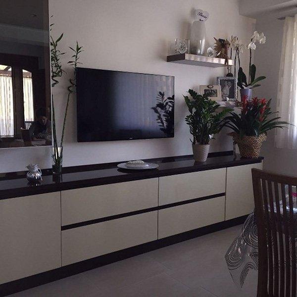 un mobile da tv marrone e beige e sopra una tv e accanto dei vasi di fiori