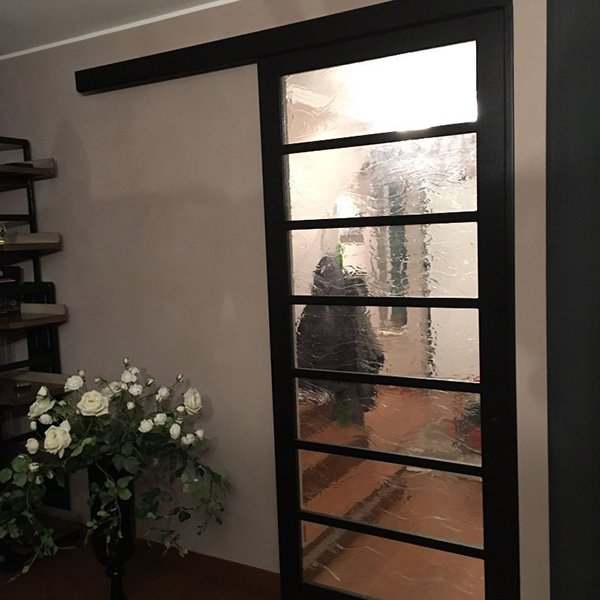 una porta di vetro con rifiniture nere e accanto un vaso di fiori bianchi