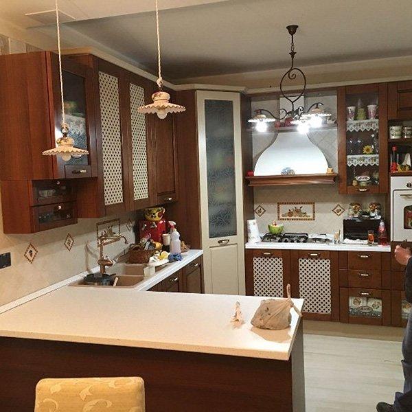 una cucina angolare color marrone e panna in legno lucido