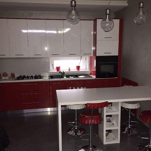 una cucina moderna di color bordeaux e bianco con un tavolo bianco con sgabelli rossi e bianchi