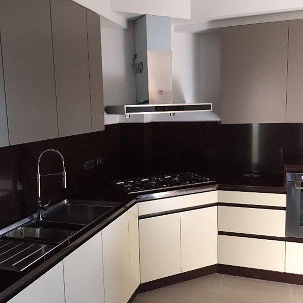 una cucina angolare color panna e legno scuro con cappa in acciaio, sotto i fornelli e sulla sinistra il lavandino