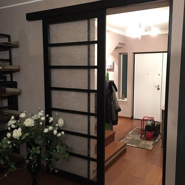 una porta in vetro con rifiniture nere aperta e sulla sinistra un vaso di fiori bianchi