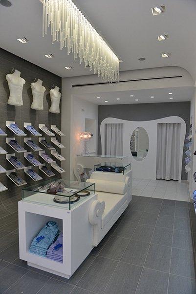 interno di un negozio con camicie esposte su dei piccoli pannelli a muro e in mezzo un divano in pelle con alle estremità due vetrine con dentro degli oggetti