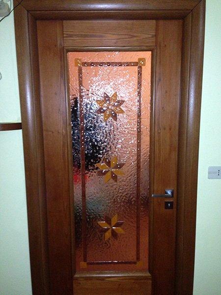 una porta in legno con al centro un vetro arancione con dei fiori disegnati