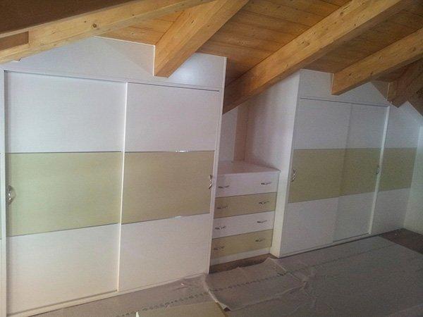 dei mobili e una cassettiera in legno lucido color panna a righe verdi e sopra la vista di un sottotetto in legno