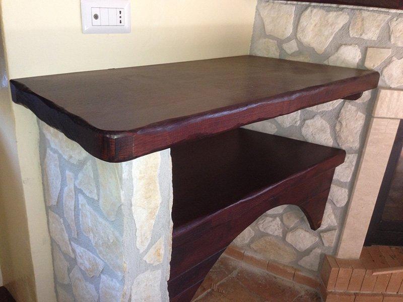 una mensola in legno color bordeaux sorretta da una piccola colonnina in pietra e sotto un mobile dello stesso colore