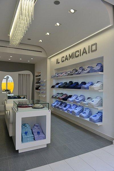 interno di un negozio con una vetrina con dentro degli oggetti e sulla sinistra delle camicie colorate esposte su dei piccoli pannelli a muro