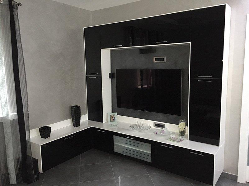 un mobile tv in legno lucido di color marrone scuro con rifiniture bianche e al centro una tv