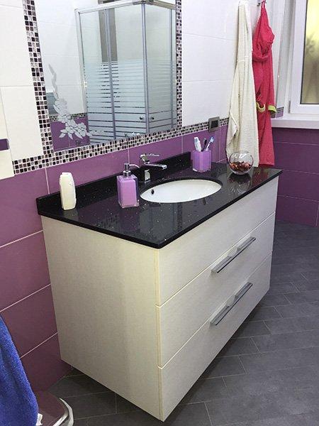 un mobile in granito nero e sotto legno lucido bianco che ospita un lavabo, sopra uno specchio e piastrelle color viola