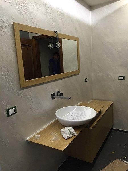 un bagno con sulla sinistra uno specchio con finiture in legno e sotto un  lavabo rotondo con un mobile marrone sotto