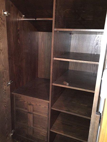 interno di un mobile in legno scuro con diverse mensole e scompartimenti