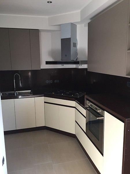 una cucina angolare color bianco e marrone scuro con una cappa in acciaio e sulla sinistra il lavandino