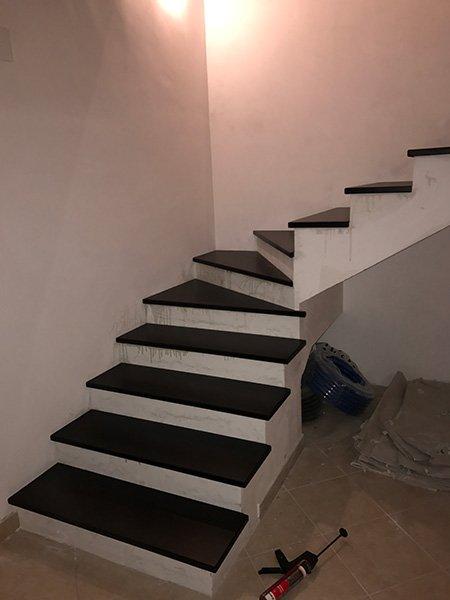 degli scalini di color marrone scuro e bianco che portano al piano superiore