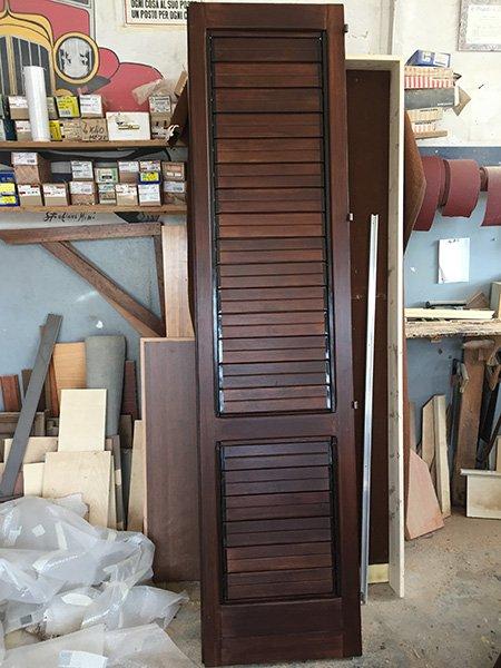 un'anta di una persiana in  legno e accanto altre assi di legno e materiale da falegnameria