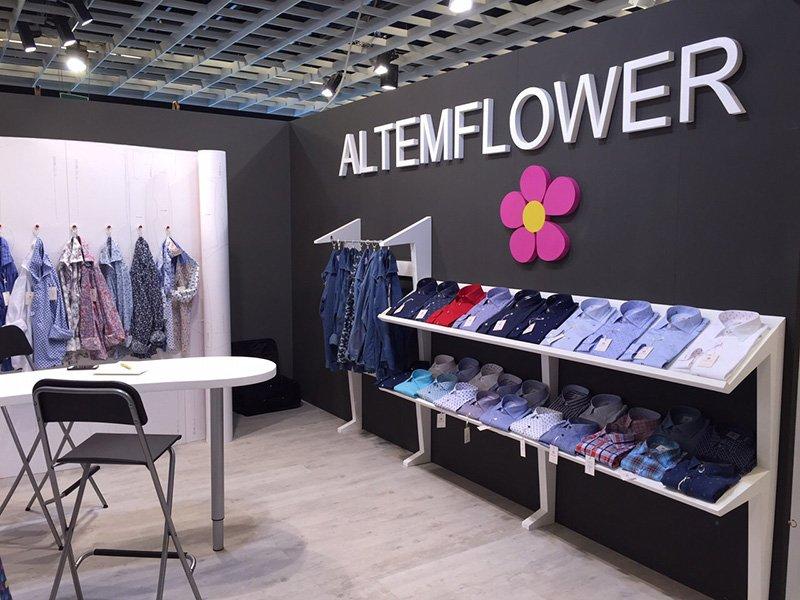 interno di un negozio con sulla destra una mensola con delle camicie esposte, sopra una scritta al muro  ALTEMFLOWER con sotto un fiore rosa, vestiti su degli
