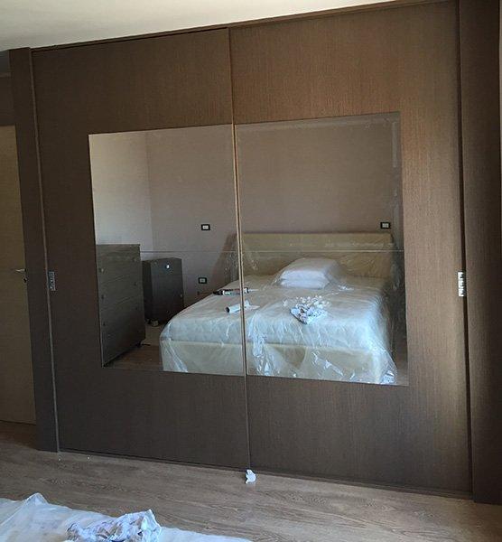 un armadio marrone a due ante con uno specchio che riflette l'immagine di un letto con sopra del celofan