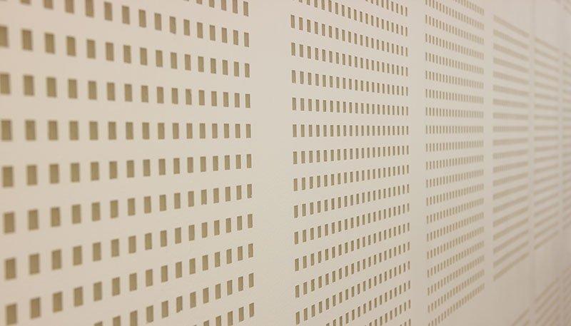 un muro con dei piccoli buchi quadrati