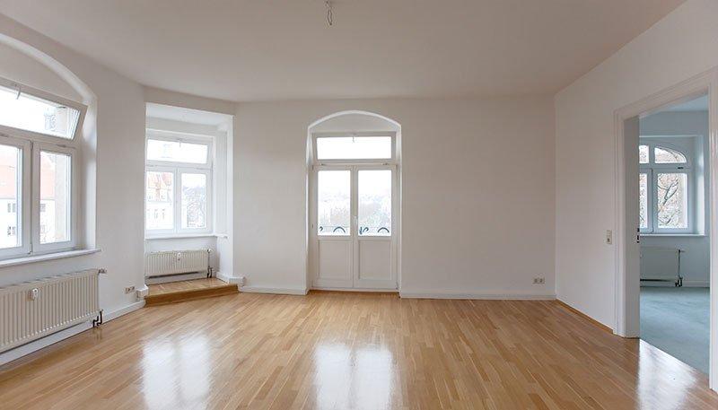 una stanza di una casa con parquet in legno, vista delle finestre e muri imbiancati