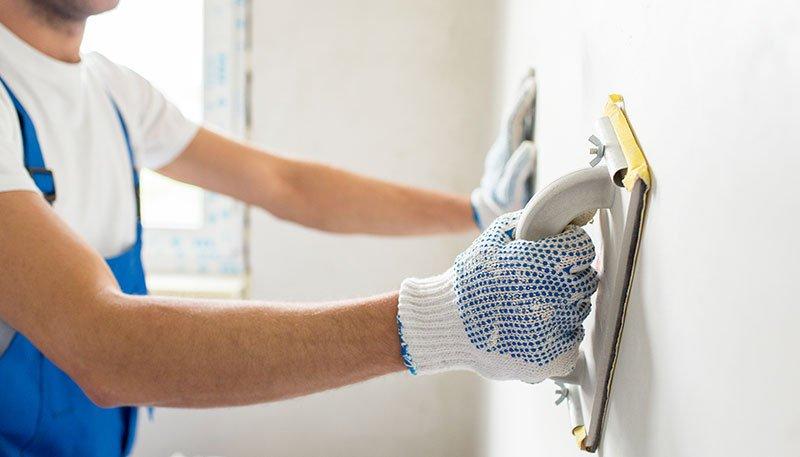 un imbianchino al lavoro su  un muro con una spatola