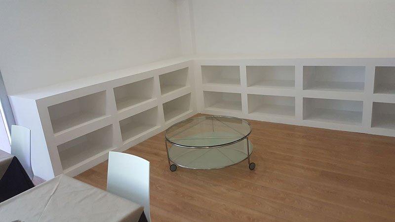 una stanza con parquet, un mobiletto bianco a L con tanti scompartimenti e un tavolino in vetro con le rotelle