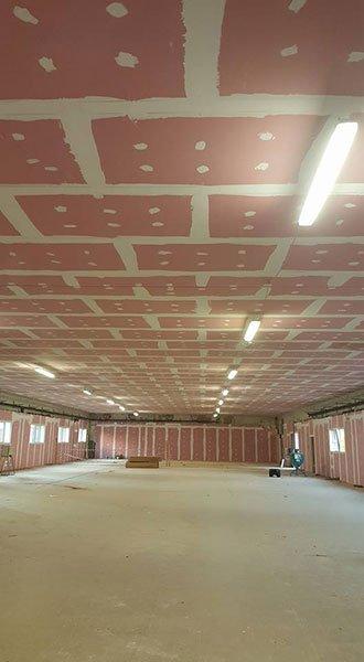 interno di un ampio stabile in costruzione con soffitti dipinti a rettangoli rosa