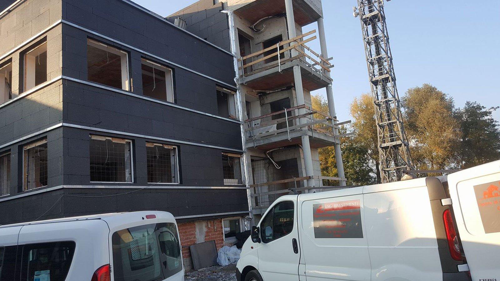 due furgoni bianchi di fronte a uno stabile in costruzione