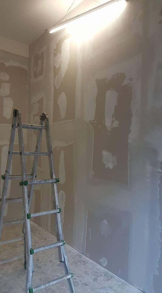 una scala di ferro in una stanza con muri da imbiancare
