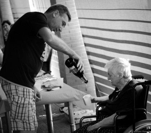 assistente versa da bere a una donna anziana