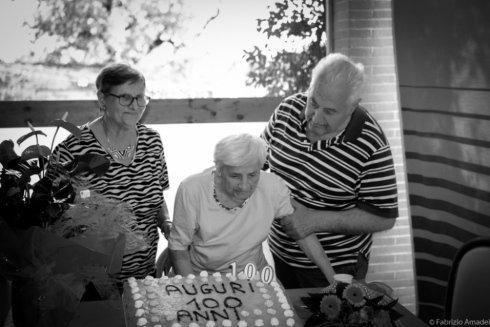 donna anziana soffia sulle candele della torta per i suoi 100 anni