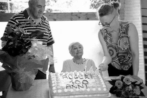 assistente di una casa di riposo accende le candele di una torta di compleanno