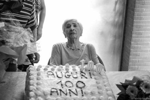 anziana in casa di riposo con torta di compleanno