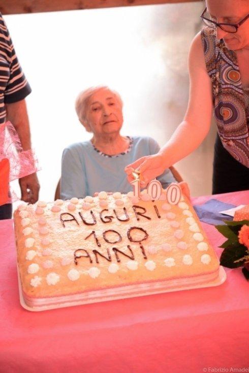 anziana con torta di compleanno per i suoi 100 anni