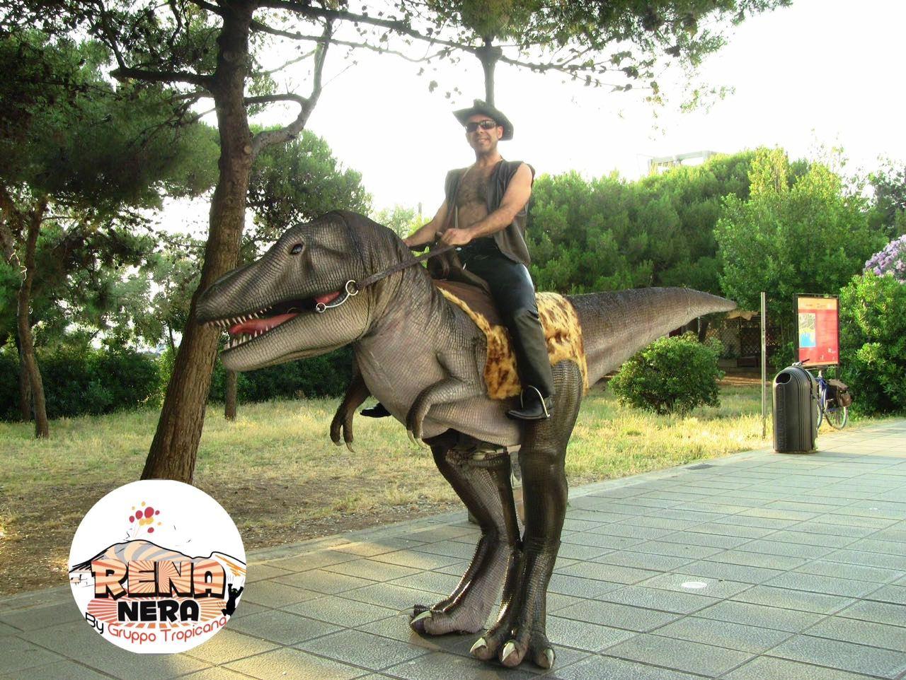 uomo che cavalca un finto dinosauro